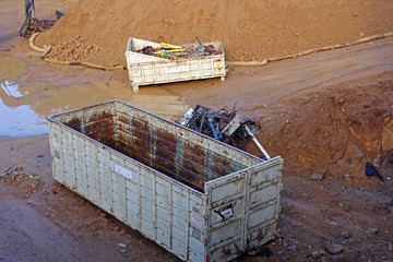 High angle view of a deep excavation site with big truck-size containers at the bottom