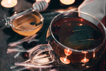 Foto op Plexiglas Alcohol Black cup tea with dried rosehip and fresh leaves mint on the background of scattered dried rose hips and wax candles. Selective focus. Close up. Autumn and winter background.