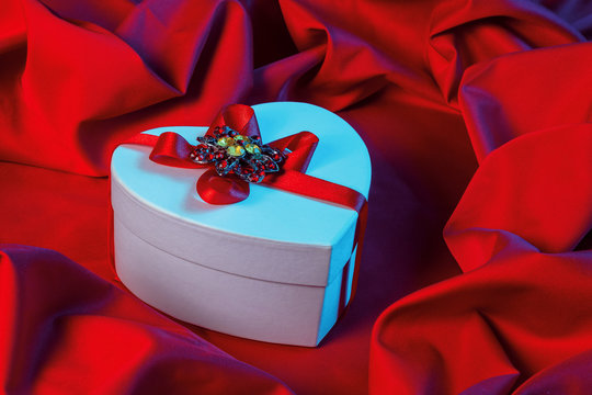 valentines greeting card in blue light. white cardboard box in shape of heart wrapped in ribbon lay on a red cloth which repeats the form of present package. love and romance gift concept