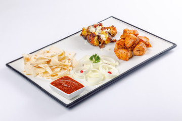 grilled chicken and baked potato with cheese. onion circles and pita bread, red sauce on a white board. great snack dish for beer