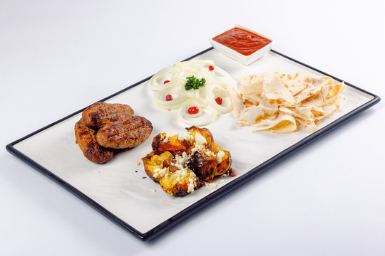 kebab and baked potato with cheese. onion circles and pita bread, red sauce on a white board. great snack dish for beer