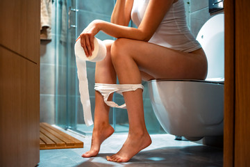 Woman sitting on toilet bowl holding tissue paper - health problem concept. Woman feel pain with constipation in WC. Closeup image of sexy young with panties pulled down sitting on toilet