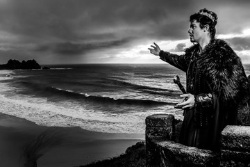 Dramatic image of king with crown standing on balcony and summoning gathering stormy skies and ocean