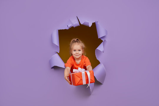 Cute little child girl breaks through a colored purple paper wall with gift box in hands. Toddler funny emotions face. Copy space for text