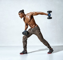 Athletic man doing exercise for arms with dumbbells. Photo of muscular fitness model working out on grey background. Strength and motivation. Full length