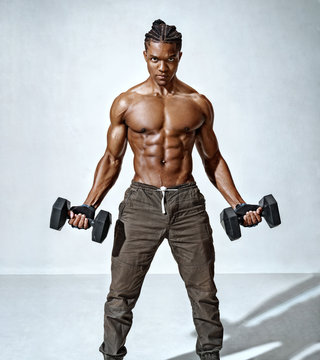 Powerful man doing the exercises with dumbbells. Photo of young man with good physique isolated on grey background. Strength and motivation