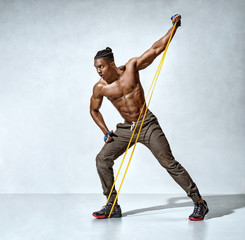 Strong man working with resistance band. Photo of man with athletic body on grey background. Strength and motivation