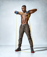 Muscular man performs exercises using a resistance band. Photo of young man on grey background. Strength and motivation. Full length
