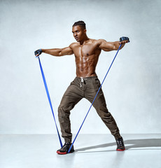 Sporty man using resistance band doing lateral raise. Photo of man with naked torso on grey background. Strength and motivation
