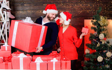 Forever love. cheerful man and woman share presents. cozy evening with your beloved. celebrate christmas together. winter season. happy new year. family holiday. couple in love santa hat. gift time