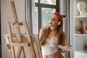 Beautiful girl singing and painting. Young beautiful woman painting artist while working in studio,...