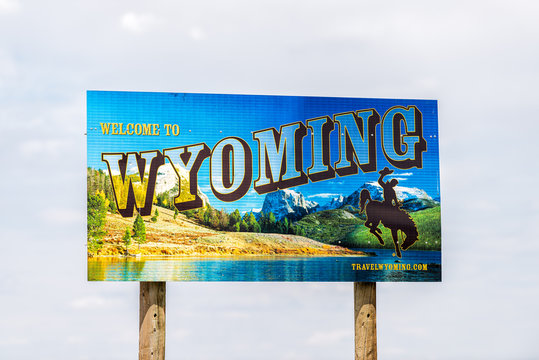 Manila, USA - July 24, 2019: Sign for welcome to Wyoming near Flaming Gorge Utah National Recreational Area Park with mountains and cowboy