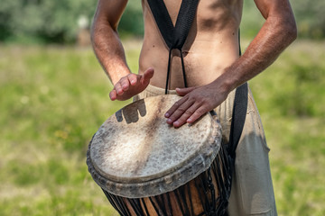 Unidentified caucasian man playing african djembe drum
