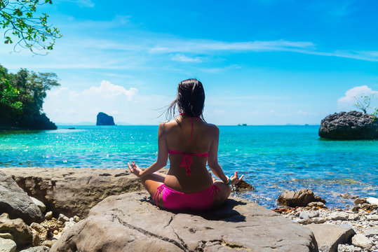 Healthy woman in bikini relaxing and practicing yoga pose on beautiful destination nature island Krabi, Wellness girl traveling Phuket Thailand beach, Tourism summer holiday vacation travel Asia trips