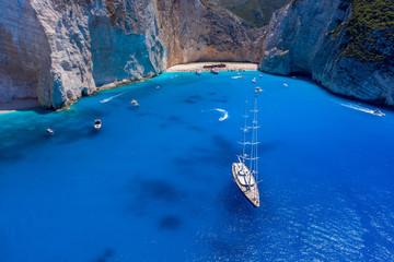 Aerial drone shot of luxury yacht leaving Zakynthos shipwreck navagio beach in summer