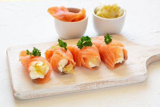 Slices of smoked salmon wrapped with cottage cheese and marinated ginger. Party snack.