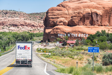 Moab, USA - August 13, 2019: Fedex truck on Utah scenic byway highway 191 road with sign on canyon cliff for Hole in the rock rest area