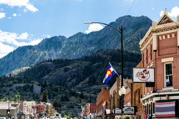 Ouray, USA - August 14, 2019: Small town in Colorado with city main street and San Juan mountains peak view by historic architecture