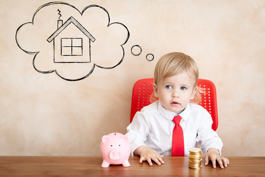 Happy child with coins and piggy bank. Funny kid playing at home. Real estate, investment and new home concept