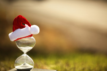 Christmas countdown. Modern Hourglass with space for text -- sand trickling through the bulbs of a crystal sand glass. Holiday-themed image.