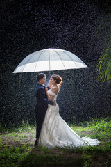 Amazing smiling wedding couple. Pretty bride and stylish groom. The bride and groom hold an umbrella on a rainy night. The groom smiled the bride. Sensual portrait of a young couple. Wedding Valentine