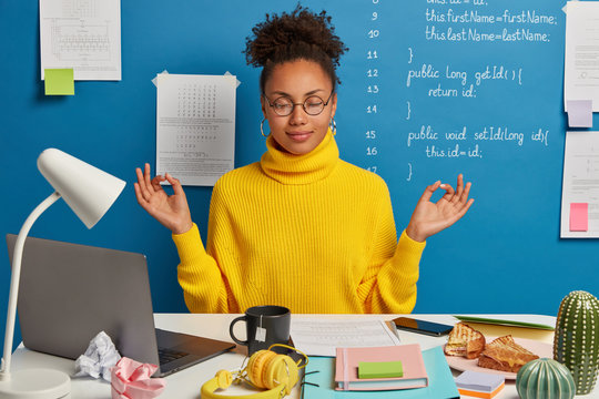 Woman freelance worker does yoga exersice at workplace, enjoys calm tranquil atmosphere, wears round glasses and jumper, gathers with thoughts, takes break after working on laptop and with papers