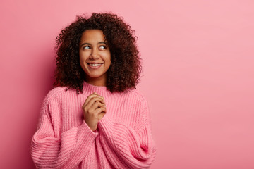 Satisfied dark skinned girl with Afro curly hair keeps hands together, focused above smiles gently wears knitted sweater dreams about something nice has cheerful thoughtful expression isolated on pink