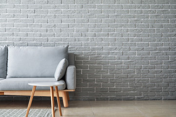 Soft couch and table near brick wall