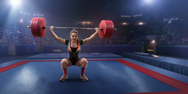 Female athlete squats with a barbell on a professional stadium. Stadium and crowd are made in 3d.