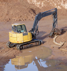 High angle view of an excavator at the bottom of a construction excavation site after the rain