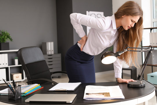 Young businesswoman suffering from back pain in office