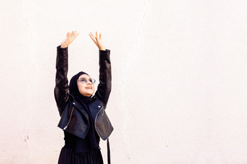 Happy Iranian girl putting hands up and dancing. Excited young female celebrating a victory. Smiling Muslim woman in traditional Islamic clothing - hijab