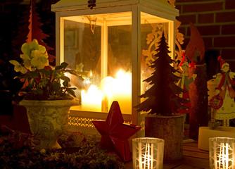 Weihnachtliche Dekoration mit Christrose und Windlicht und Kerzenschein