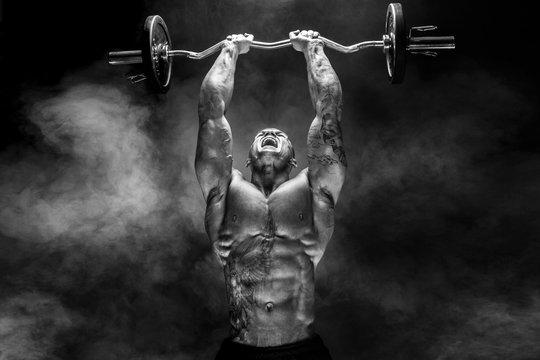 Portrait of muscular man lifting dumbbell. Studio shot. Exercise for triceps. Motivation.