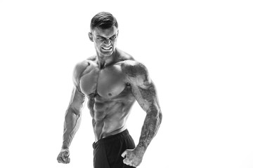 Tattooed muscular super-high level handsome man posing in studio isolated on white background