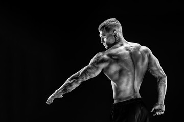 Very brawny guy bodybuilder posing. Beautiful sporty guy male power. Fitness muscled man showing his back in studio. Dark background.