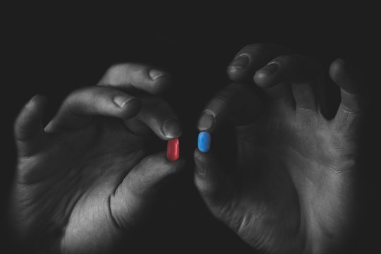 Man holding red and blue pills in hand isolated on black background.  Medicine concept and pills, copy space