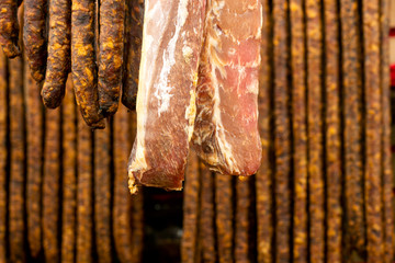 Hanging pork meat and sausages in smokehouse for sale at the winter Christmas market