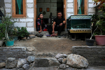 Solihatun and husband Nasroh sit in their newly-raised house as they pose for pictures at Tambakrejo, a village affected by land subsidence and rising sea level, in Semarang