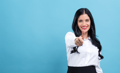 Young woman giving thumb up on a blue background