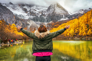 Back side of asian traveler woman looking and sightseeing over the Pearl Lake with snow mountain in autumn season in yading nature reserve, China.travel and tourism,famous place and landmark concept