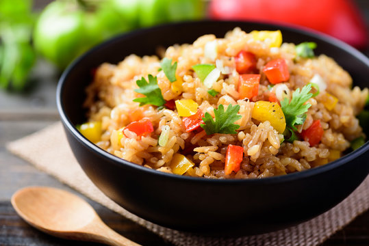 Fried rice with vegetables in a black bowl, Asian food