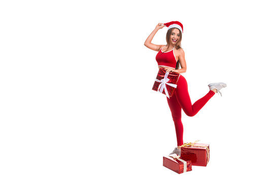 Portrait of young, sexy and beautiful woman in sport suit and Santa hat. White background. Christmas, xmas, x-mas gifts concept