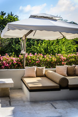 outdoor garden seating in a garden with pillows and many trees