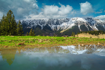 Wall Mural - Alpine spring landscape with snowy mountains in background, Transylvania, Romania