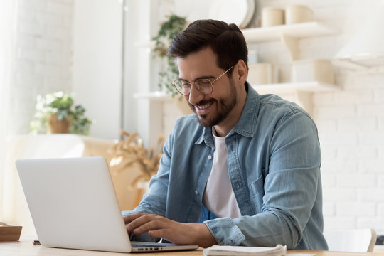 Smiling young man using laptop studying working online at home