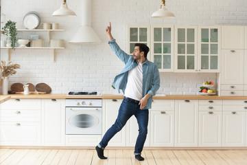 Carefree funny young man having fun dancing alone in kitchen Papier Peint
