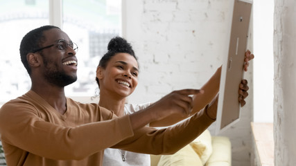 Excited biracial couple decorating new home together