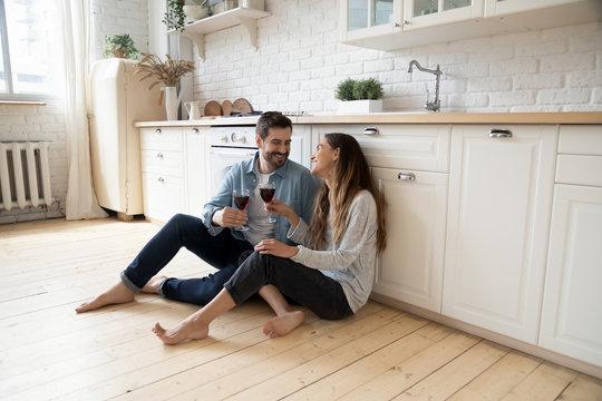 Romantic couple sit on warm kitchen floor talking drinking wine