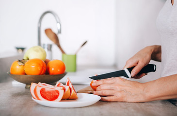 Young woman's hands chopping grapefruit using a knife and cutting board in modern kitchen close up image. Plenty of apples, grapefruits, kaki and oranges fruits are on the plate. Wall mural